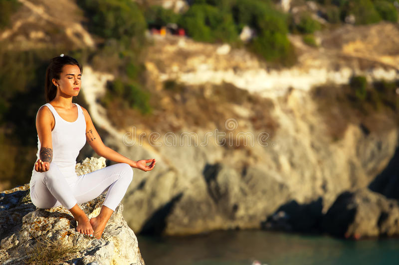 Yoga woman meditating at sunset or sunrise in black sea Crimea. Female model meditating in lotus position. Healthy wellness lifestyle image with multicultural stock photography