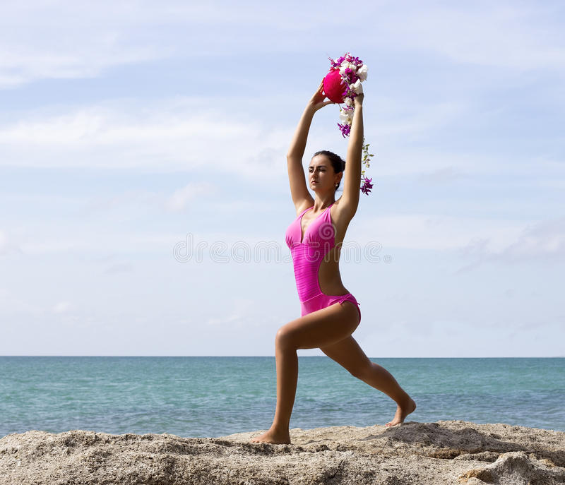 Yoga woman poses on beach near sea in pink royalty free stock photography