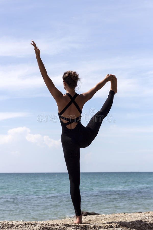 Yoga woman poses on beach near sea and rocks stock images