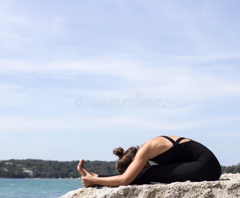 Yoga woman poses on beach near sea and rocks royalty free stock photography