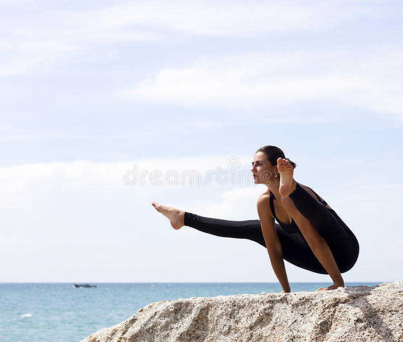 Yoga woman poses on beach near sea and rocks royalty free stock images