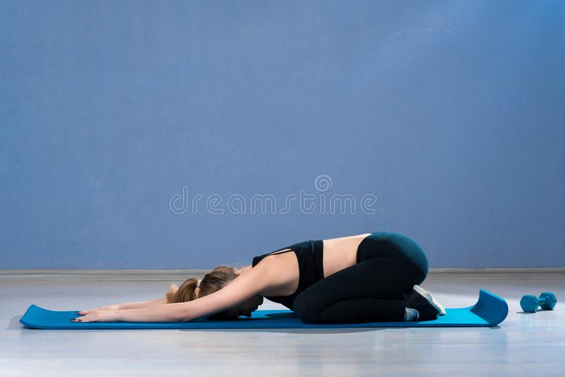 Yoga woman practices in a training hall royalty free stock photo