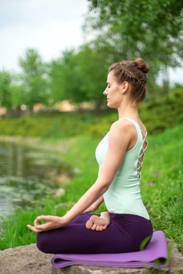 Yoga woman practicing yoga lesson, breathing, meditation, doing exercise Ardha Padmasana, half lotus pose with mudra gesture, royalty free stock image