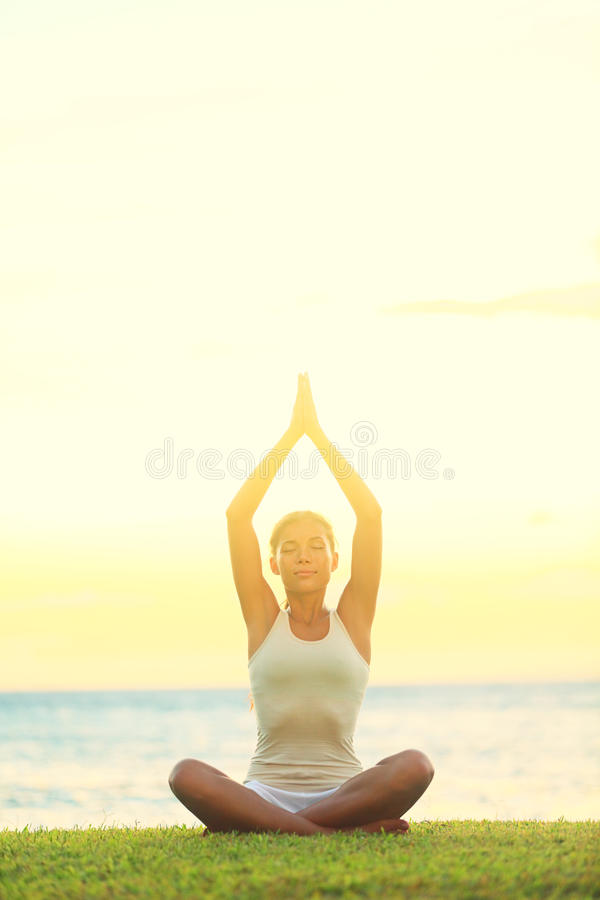 Yoga woman relaxing by sea. At sunrise or sunset doing the Sukhasana, easy pose facing water. Woman meditating in beautiful ocean landscape retreat. Meditation stock photo