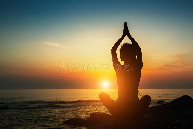 Yoga woman silhouette. Meditation on the ocean. Relax. Yoga woman silhouette. Meditation on the ocean during amazing sunset stock photography
