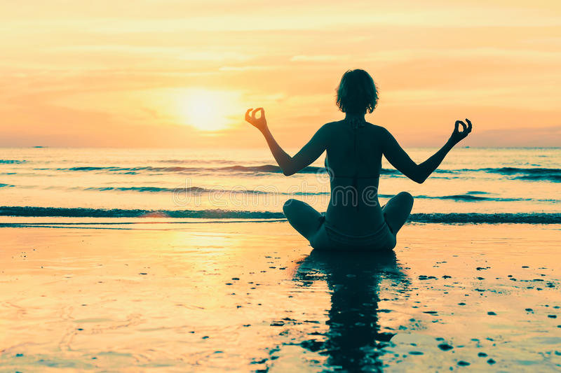 Yoga woman silhouette on the sea beach stock images