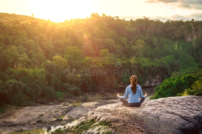 Yoga woman sit in lotus pose on mountain peak rock at sunrise royalty free stock photos