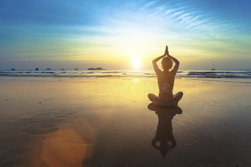 Yoga woman sitting in lotus pose on the beach with reflection during sunset. royalty free stock photos