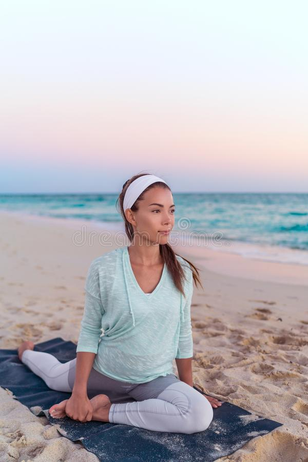Yoga woman stretching legs doing pigeon pose leg stretch on beach at morning sunrise. Fitness healthy lifestyle. Happy and serene stock photos