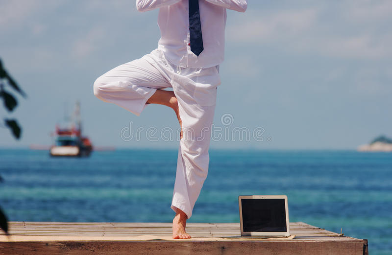 Yoga on a wooden bridge with a laptop. Businessman doing yoga on a wooden bridge with a laptop stock photo