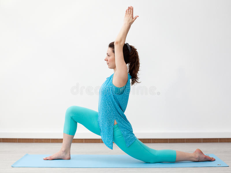 Yoga. Young brunette woman in warrior pose royalty free stock photography