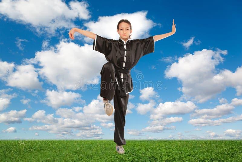 Yoga young girl in ushu pose on meadow