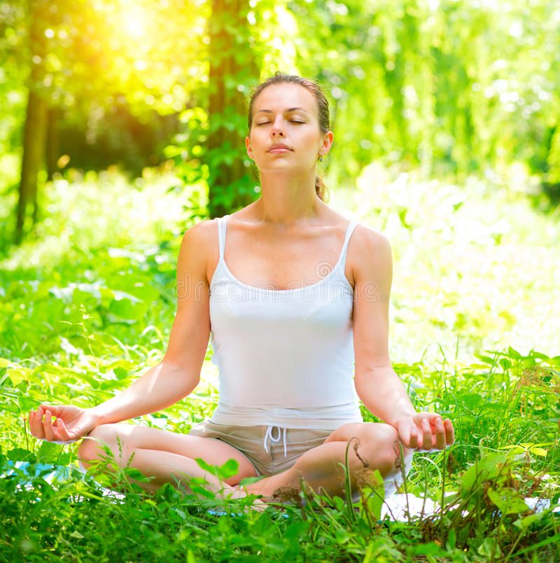 Yoga. Young woman doing yoga exercises outdoors royalty free stock photography