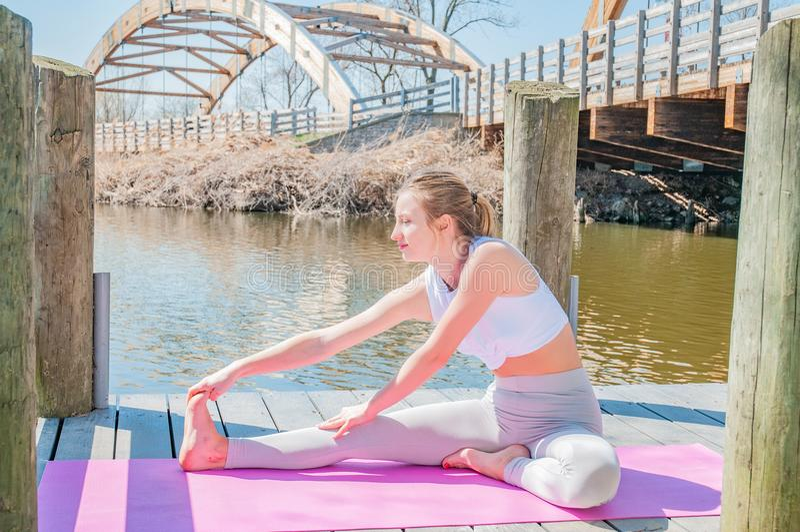 Yoga. Young woman practicing yoga Janu Sirsasana pose. royalty free stock photo