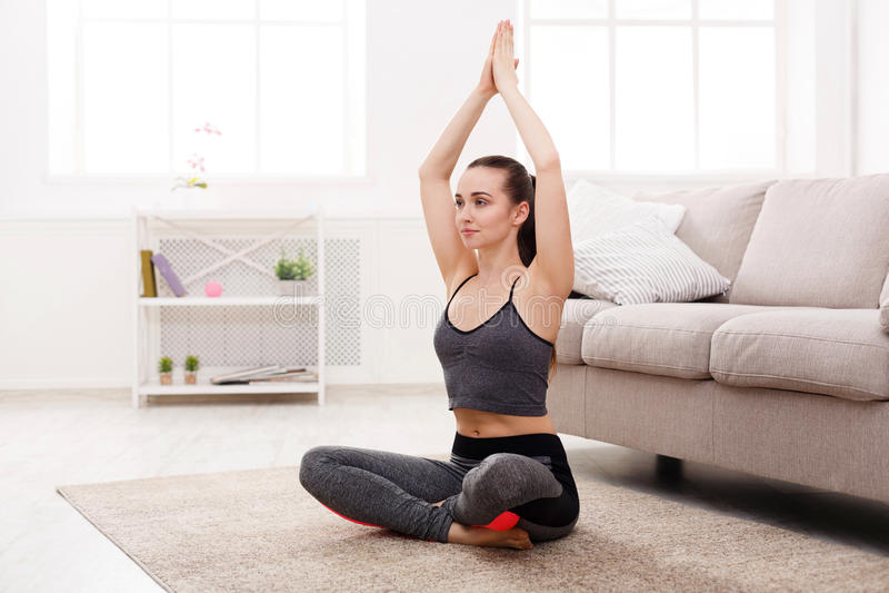 Yoga zu Hause, Frau tut Lotoshaltung stockbilder