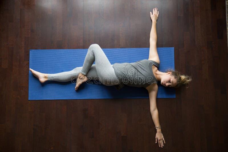 Yoga zu Hause: Haltung Jathara Parivartanasana lizenzfreie stockfotos