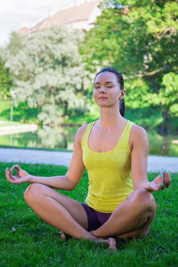Yogaconcept - de gelukkige jonge vrouwenzitting in lotusbloem stelt in park royalty-vrije stock foto's