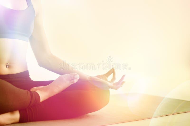Yogaflicka som inomhus mediterar och gör ett zensymbol med hennes hand Closeupen av kvinnakroppen i yoga poserar royaltyfria foton