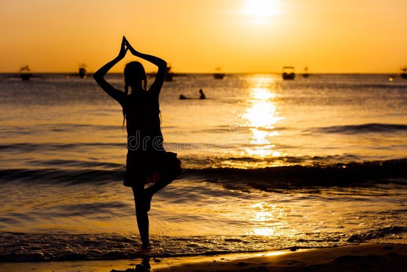 Yogaflickakontur på havsstranden på solnedgången royaltyfri bild