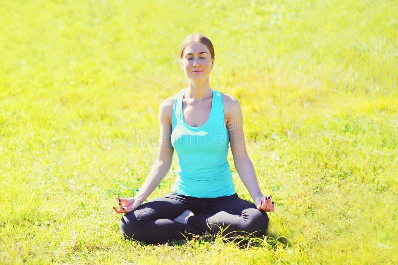 Yogaflickan mediterar sammanträde på gräs poserar lotusblomma i sommardag arkivfoto