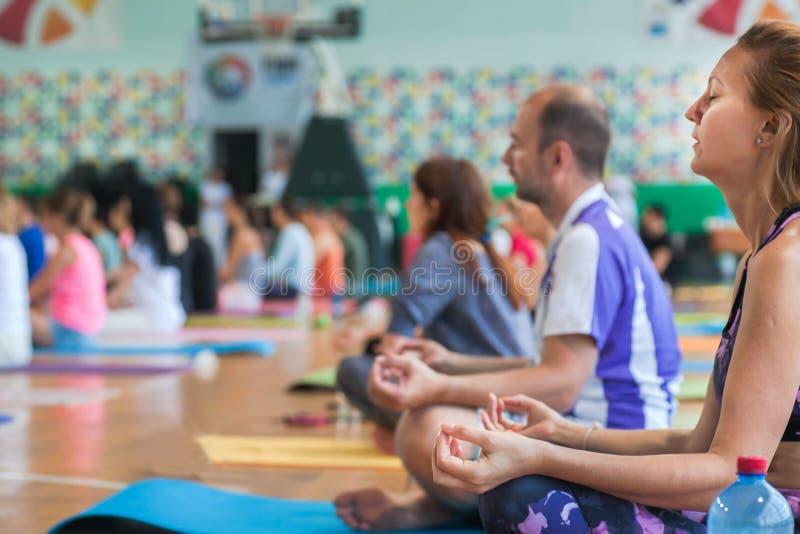 Yogafolk som gör övning av meditation och djup andedräkt som sitter i asana inom konditionklubban royaltyfri foto