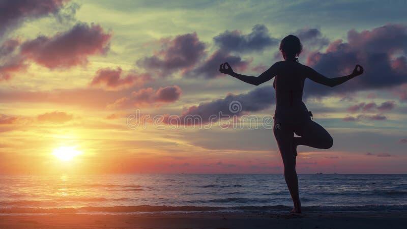 Yogafrau, die auf dem Strand während eines erstaunlichen Sonnenuntergangs trainiert stockfotos