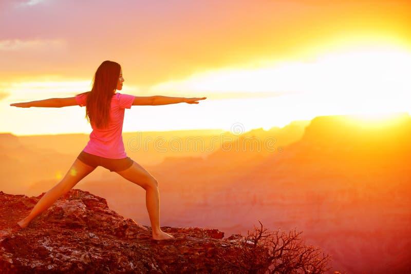 Yogafrau, die bei Sonnenuntergang in Grand Canyon meditiert stockbild
