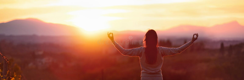 Yogafrau, die bei Sonnenuntergang meditiert lizenzfreie stockfotos