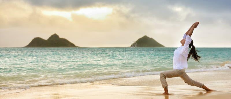 Yogafrau, die im Krieger meditiert, den ich am Strand aufwerfe stockfotografie