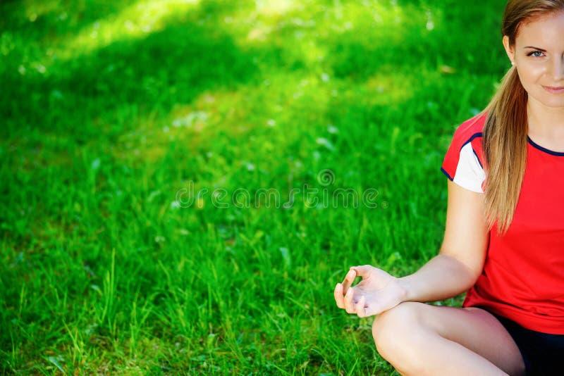 Yogafrau, die im Park meditiert lizenzfreie stockfotografie