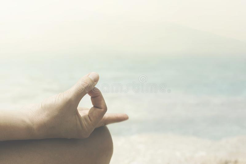 Yogagest av händerna av en kvinna som vänder mot havet arkivbild