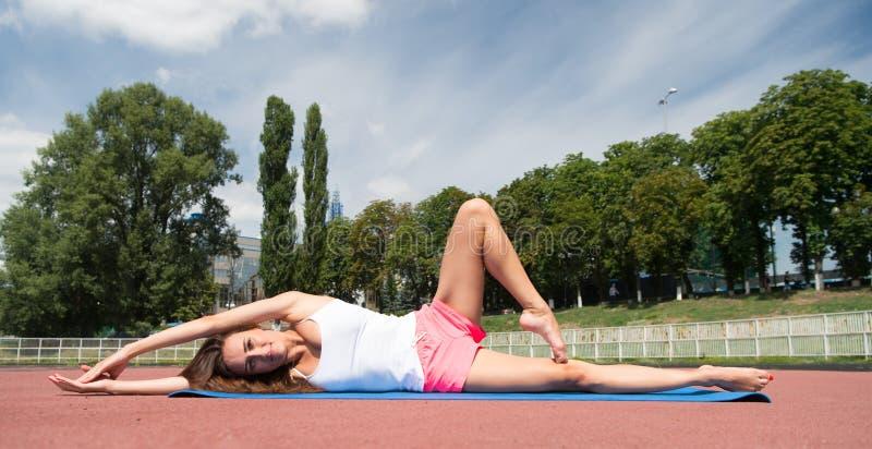 Yogahilfsentdeckungsharmonie Körper-Praxisyoga der Frau legt flexibles Naturhintergrund der Eignungsmatte draußen Mädchenausdehne stockfotografie