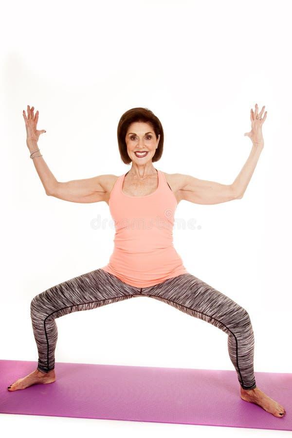 Yogahocke der älteren Frau bewaffnet oben lizenzfreies stockfoto