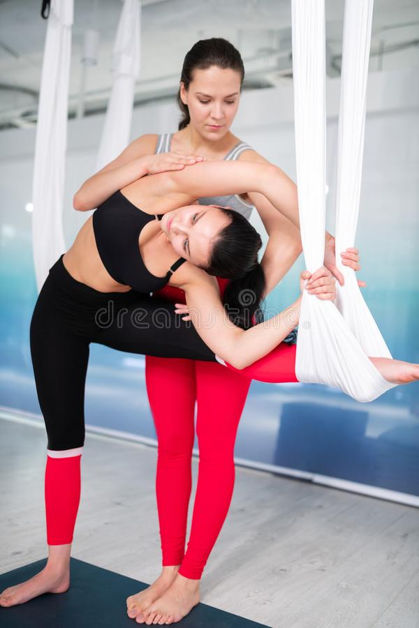 Yogainstruktör i röd damasker som hjälper hennes klientsträckning arkivbilder