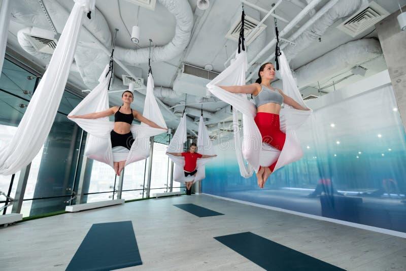 Yogainstruktör i röd damasker som visar hennes studenter flyg- övning arkivfoton