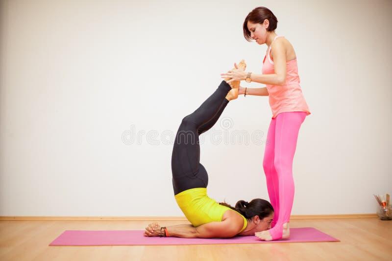Yogainstruktör som hjälper en student royaltyfria foton
