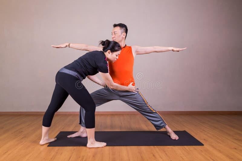 Yogainstruktör som korrigerar utförande krigare 2 för student eller Virab arkivfoto