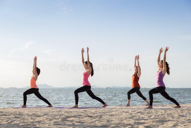 Yogaklasse openlucht op het zandige strand bij zonsondergang, Gezonde Lifestyl stock fotografie
