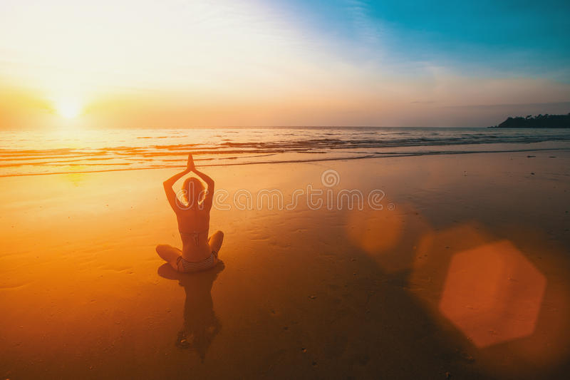 Yogakonturn av kvinnan i Lotus poserar på solnedgångstranden relax arkivbild