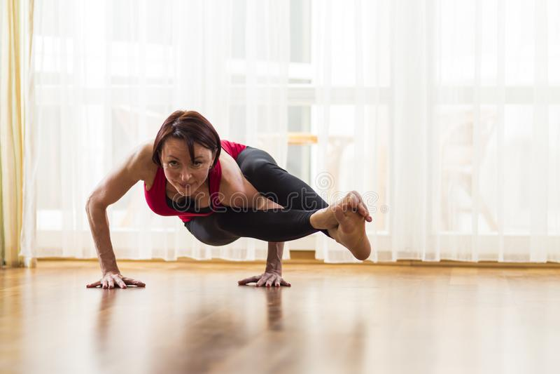 Yogakonzepte Kaukasische Frauen-übende Yoga-Übung zuhause am hellen Nachmittag Sitzen in Ashtavakrasana-Haltung während lizenzfreies stockbild