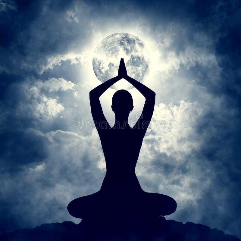 Yogakroppen poserar konturn över den sluga månenatten, meditationövning royaltyfri bild