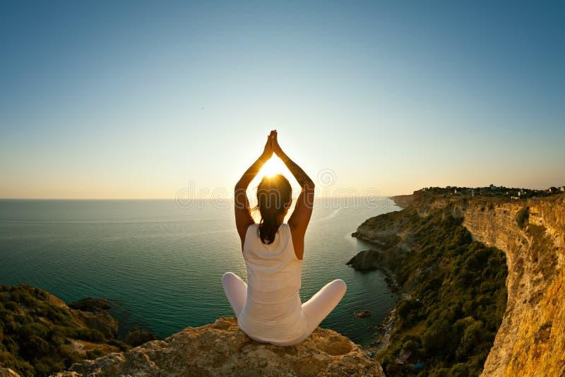 Yogakvinna som gör yoga på bakgrund av naturen och havet arkivbild