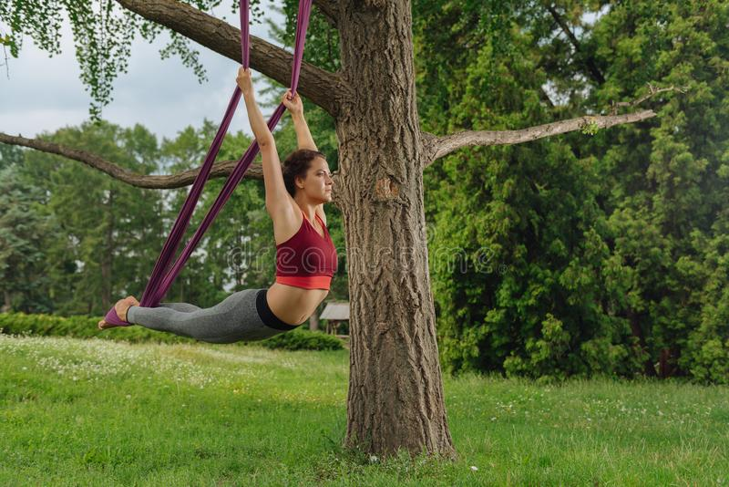 Yogakvinna som tillbaka sträcker henne medan praktiserande klipsk yoga royaltyfria foton
