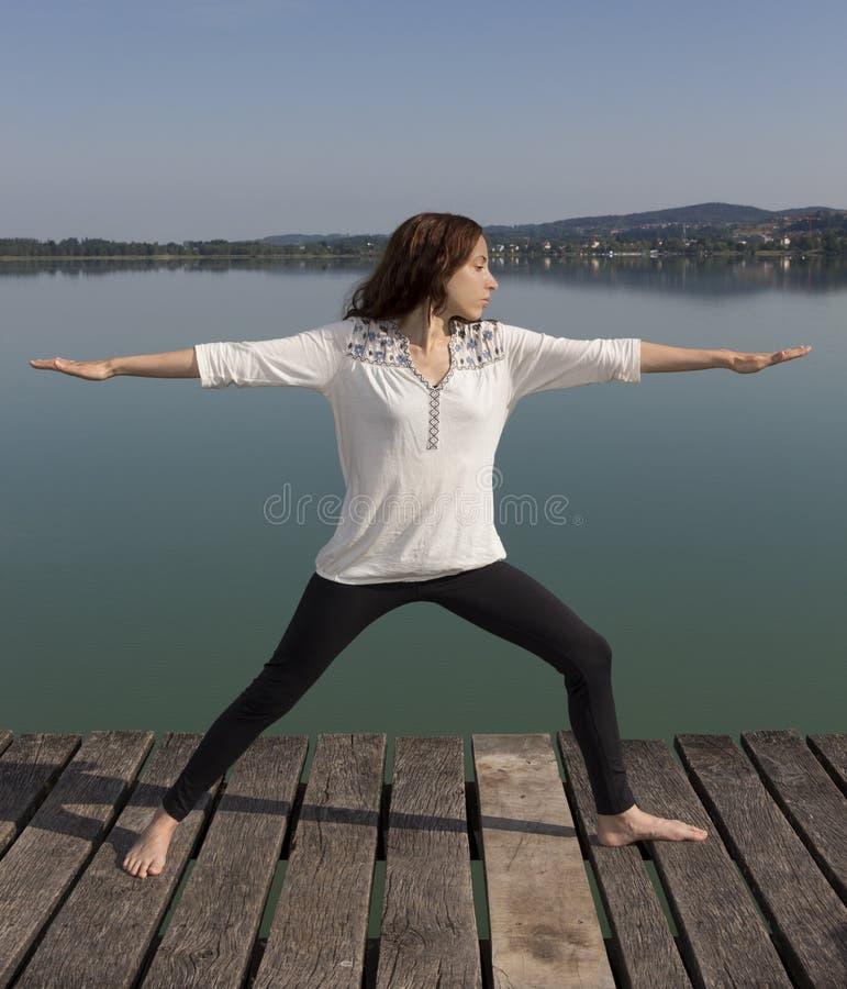 Yogakvinnan i krigare II poserar i natur fotografering för bildbyråer