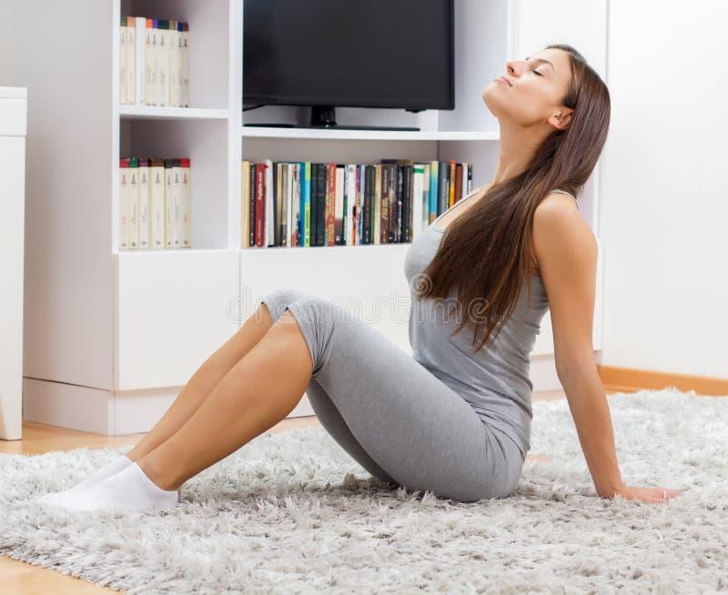 Yogakvinnan kopplar av sund livsstil arkivbild