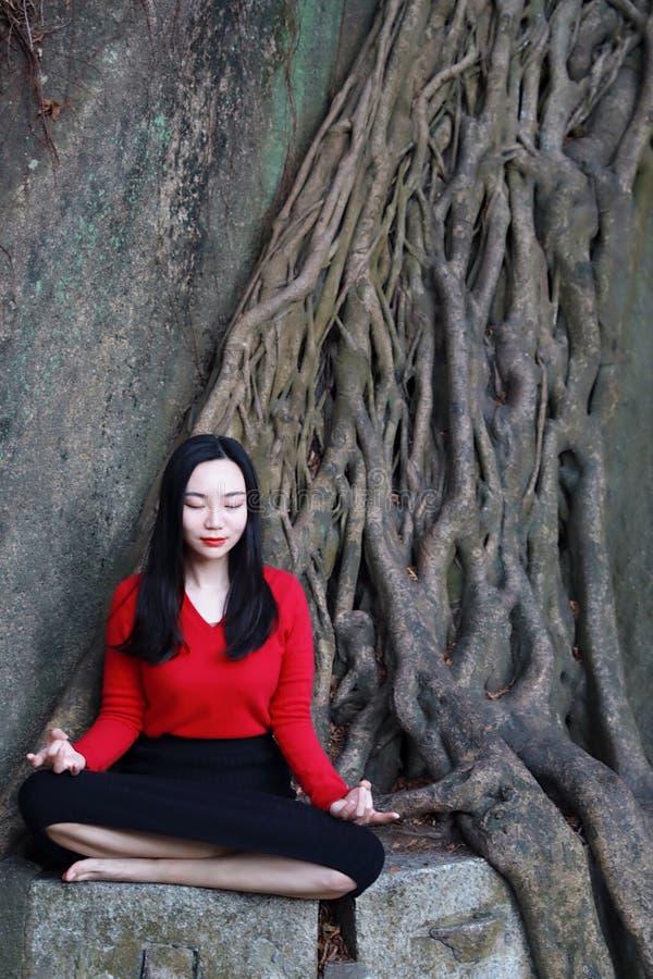 Yogakvinnan sitter i meditation poserar på bergmaximum vaggar royaltyfri foto