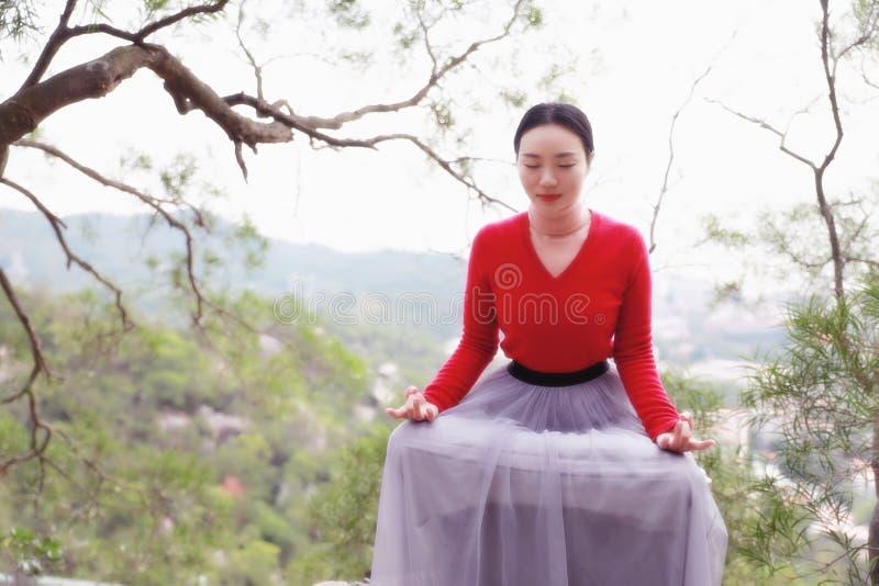 Yogakvinnan sitter i meditation poserar på bergmaximum vaggar arkivbilder