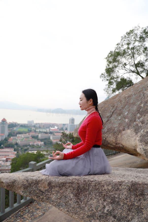 Yogakvinnan sitter i meditation poserar på bergmaximum vaggar royaltyfria bilder