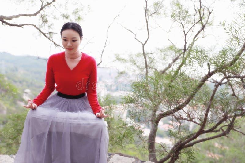 Yogakvinnan sitter i meditation poserar på bergmaximum vaggar arkivbild
