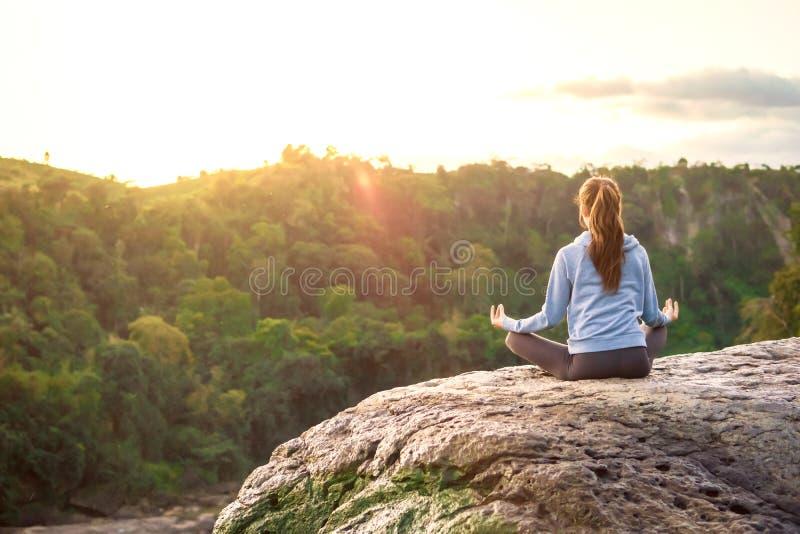 Yogakvinnan sitter i meditation poserar på bergmaximum vaggar på soluppgång royaltyfri foto
